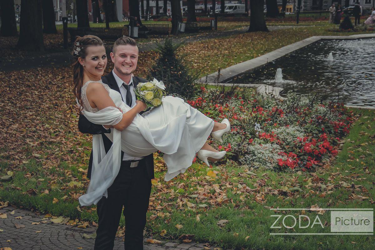 Hochzeitsfoto - Der Bräutigam trägt seine Braut - und die Kamera ist live dabei
